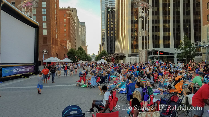 Raleighites sit all over City Plaza waiting to watch a movie on a large inflatable screen. July 2016.