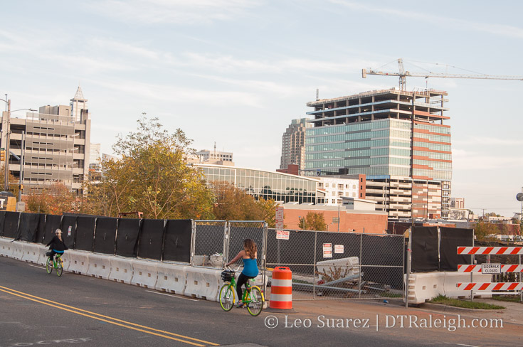 Limebike riders pass in front of the former warehouse of Shelton's Furniture on Morgan Street, November 2017.