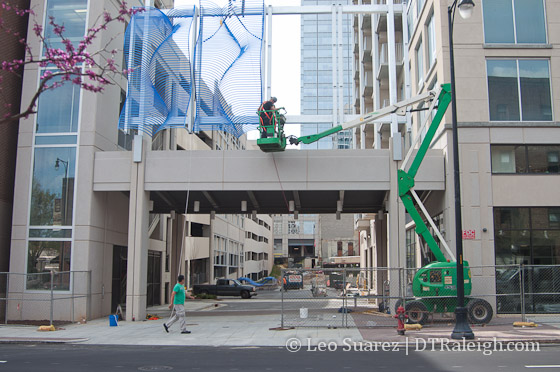 Artwork being installed over the vehicle entrance along Blount Street.